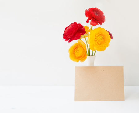 Buttercup red and yellow flowers in vase over white background.