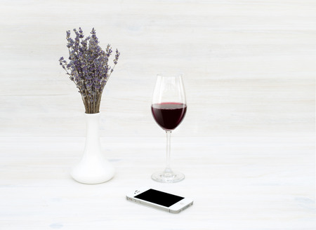4s: SEVASTOPOL, UKRAINE - MAY 7, 2015: An iPhone 4S smartphone photographed on a wooden table with glass of wine  and bouquet of lavender. Editorial