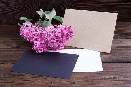 syringa: Syringa flowers with empty color paper on wooden table.