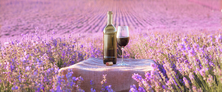 wine colour: Bottle of wine against lavender landscape in sunset rays.