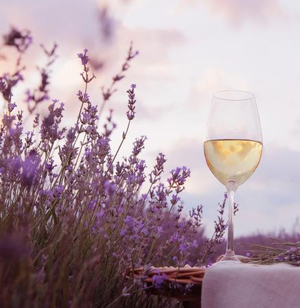 Wine glass against lavender landscape.