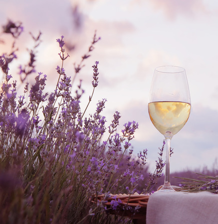Wine glass against lavender landscape.