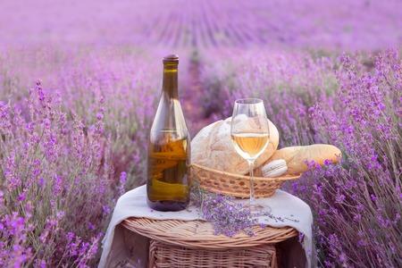 Bottle of wine against lavender landscape in sunset rays.