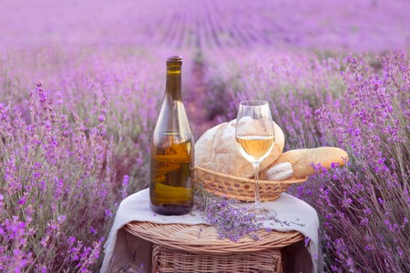 Bottle of wine against lavender landscape in sunset rays.