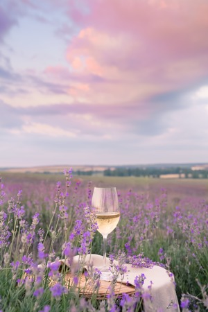 autumn food: Wine glass against lavender landscape in sunset rays.
