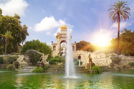 waterfall in the city: Fountain in a Parc de la Ciutadella with shining sun, green water and cloudy blue skies. The Parc de la Ciutadella (Ciutadella Park) is a park in Ciutat Vella, Barcelona, Spain.
