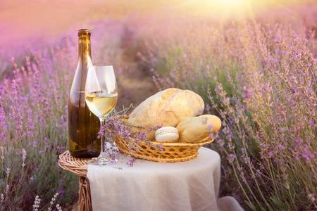 Botella de vino tinto y copa de vino en el suelo. Botella de vino contra el paisaje de lavanda. Cielo azul sobre el campo de lavanda en Provenza, Francia.