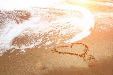 heart in sand: Soft wave of blue ocean on sandy beach. Heart drawn on the sand of the beach with sea foam and wave. Romantic vacation. Stock Photo