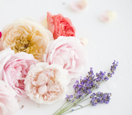 Summer flowers composition of red roses and violet lavender over white. Blooming lavender on white table. Bouquet of lavender. Provence interior.