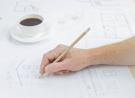 Architectural background. Human hand with pencil over blueprints with sketches of projects.