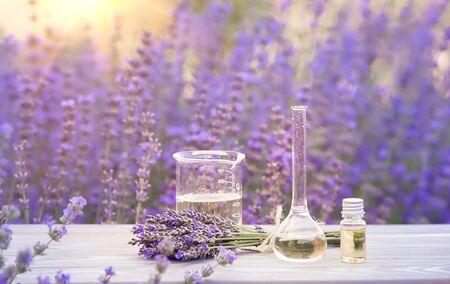 Ätherisches Lavendelöl in der Flasche mit Tropfer auf dem grauen Holzschreibtisch. Horizontale Nahaufnahme. Standard-Bild