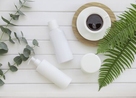 Skin cream bottles over wood background with tropical fern and eucalyptus Stock Photo