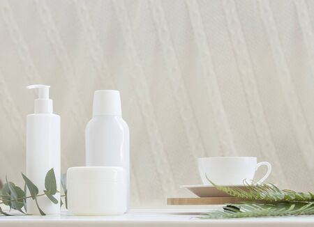 Natural cosmetics and leaves of fern and eucalyptus on a light background.