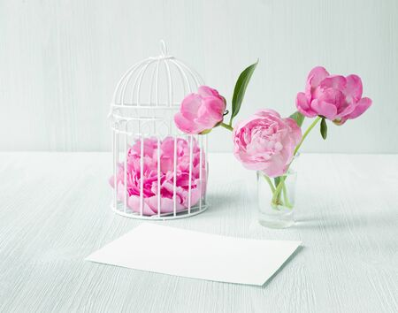 White bird cage twith petals on wooden table. Three peonies flowers in glass vase. Empty invitation card for marriage celebration. Clean scandinavian style decoration.