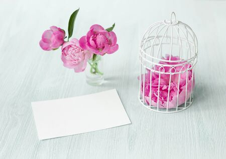 Small bird cage with peony flower bouquet, invitation card template with text space, Modern scandy style interior.