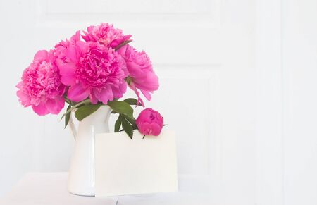 Pink peonies in white enamelled vase. Beautiful flowers in interior design. White paper for invitation text, white peonies in a vase, interior decoration.