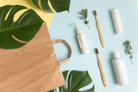 Natural eco cosmetics, morning accessories and leaves of monstera and eucalyptus on a blue