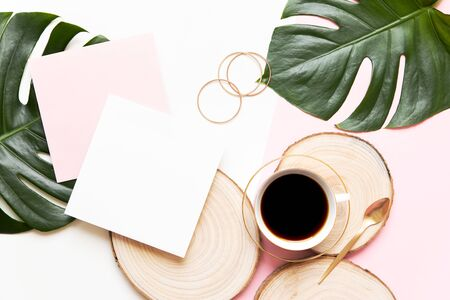 Creative flat lay of workspace desk. Tropical eucalyptus leaves, paper card and envelope on beige background.