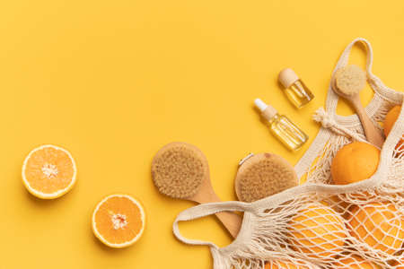 Fresh oranges and brushes in a eco bag. Essential oil in a glass bottle for massage. Cutted citrus fruit for natural cosmetics