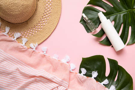 Tropical palm tree leaf on a pink background. Sunscreen and hat in composition with monstera leaves.Vibrant minimal fashion concept. Banque d'images