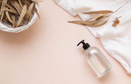 Transparent bottle mockup on pastel pink background with eucalyptus leaves.