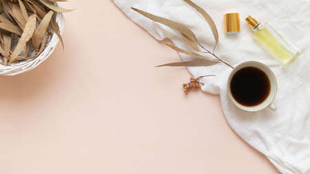 Eucalyptus leaves and a cup of black coffee with a bottle of essence on a light background with empty space