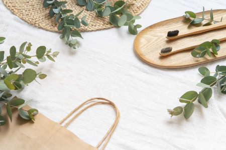 Bambool toothbrush on wood plate and tote bag. Leaves of eucalyptus on a light fabri� background. Banque d'images