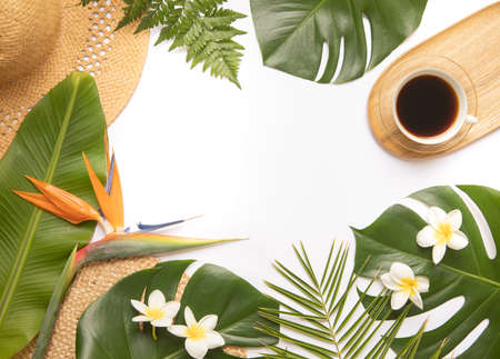 Cup of black coffee with fresh tropical leaves.