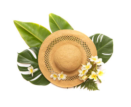 Tropical palm tree leaf and hat on a white background. Flower in composition with monstera leaves. Vibrant minimal fashion concept