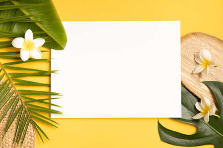 Tropical mockup palm leaves and paper card on yellow background.