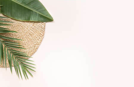 Round wicker stand and palm leaves on pink background. Fltlay style concept with text place