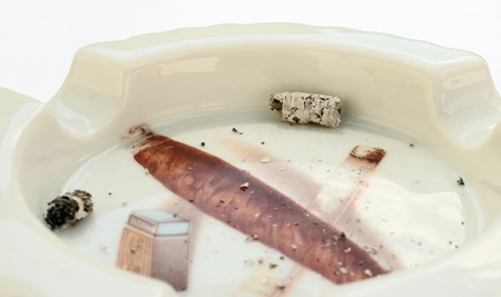 Ash flicked off to unusual ashtray isolated on white background. Stock Photo