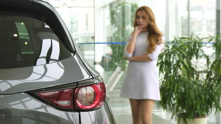 Selective focus on car lights gorgeous sexy woman in a dress looking at the auto thoughtfully decising which automobile to buy consumerism client customer purchasing sales rental retail.