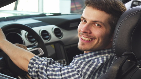 Close up shot of a young male driver using his smart phone sitting in a new convertible, smiling happily to the camera. Attractive young man enjoying his newly bought convertible auto.