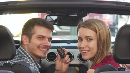Joyful young couple sitting in their new convertible examining the car smiling to the camera happily showing car keys. Cheerful couple buying a new automobile at the dealership.
