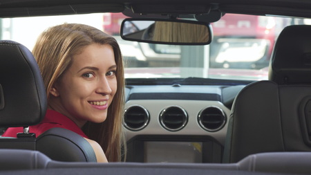Shot of a gorgeous young woman smiling playfully to the camera over her shoulder sitting in her newly bought convertible. Driving, travelling, retail, sales concept. Stock Photo