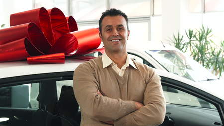 The man folded his arms and looked around. Behind him is a car. The car is tied with a big red bow. At the end he looks at the camera and smiles Foto de archivo