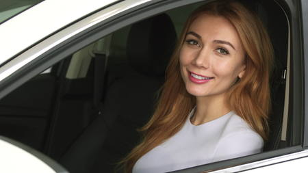 Attractive young sexy woman using smart phone sitting in her car smiling to the camera technology communication safety driving online automotive rental service connection mobility travelling.