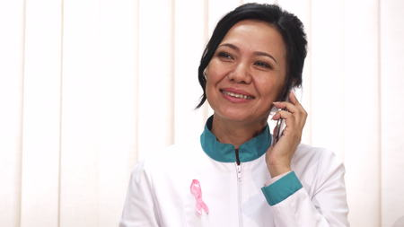 Beautiful happy mature Asian female doctor with pink ribbon cancer awareness symbol on her lab coat smiling talking on the phone receiving good news positivity health medicine job. Stock fotó