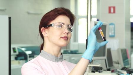 Cerca de una hermosa bióloga que se prepara para una encuesta médica que examina dos tubos de ensayo llenos de muestras de sangre. Medicina, salud, concepto de encuesta clínica.