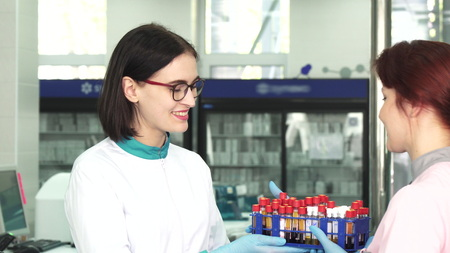 Young beautiful female biologist handing a stack full of blood samples test tubes to her coworker at the laboratory. Medicine, healthcare, immunology, microbiology concept.