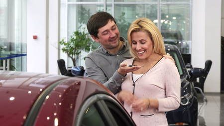 Mature man covering eyes of his wife at the dealership presenting her a new car as a gift happiness car keys ownership driving emotions love family travel driving.