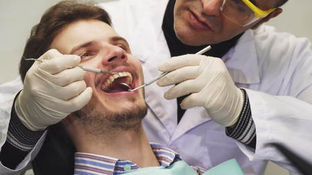 Cropped close up of a handsome young man having his teeth examined by a professional dentist at the clinic medicine health clinical appointment patient dentistry trust occupation service. Archivio Fotografico