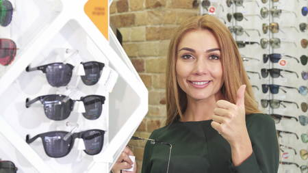 Happy beautiful red haired woman smiling excitedly showing thumbs up choosing sunglasses