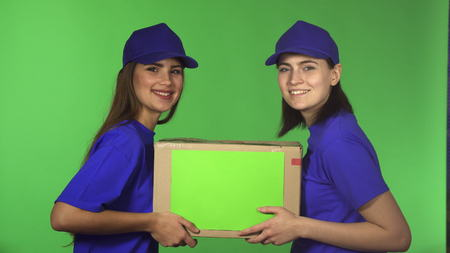 Young happy beautiful delivery service female workers smiling joyfully to the camera delivering cardbord box with a copyspace holding the package occupation postal concept.