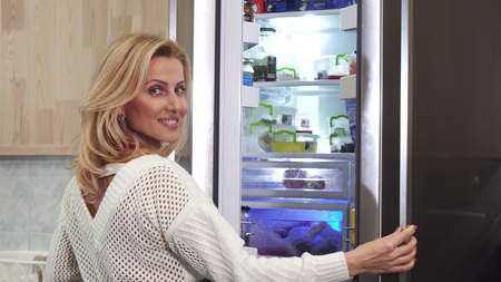 Achteraanzicht shot van een mooie rijpe vrouw die de koelkast opent in de keuken die zich voorbereidt om voedsel te koken voor haar familie thuis glimlachend naar de camera over haar schouder eten gezonde levensstijl voeding. Stockfoto