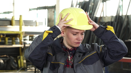 Young beautiful female engineer looking tired and exhausted taking off her hardhat after work exhaling heavily. Tiredness, stress, overworking, industry, distribution concept.