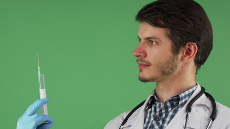 Cropped shot of a handsome bearded male doctor preparing syringe for an injection. Attractive therapist posing with a syringe on chromakey background. Medicine, healthcare, vaccination concept.
