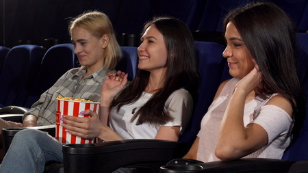 Young attractive woman looking angry when her friends grabbing popcorn from her bucket at the cinema. Annoyed young woman slapping hands of her friends, while they eat her popcorn.