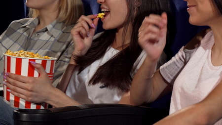 Cropped sliding shot of three young cheerful women enjoying watching comedy movie at the local cinema. Female friends relaxing at the movie theatre. Teenagers, weekend concept. Reklamní fotografie